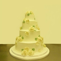 White Roses And Green Blosom royal iced 4 tier wedding cakewhite marzipan rosesroyal iced green blossom