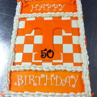 Tennessee Vols Logo Cake Butter cream cake with chocolate and fondant accents. The checkerboard pattern and smaller 'T's are made from white chocolate....