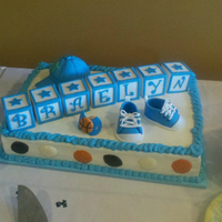 Sports-Themed Baby Shower Cake This was a half sheet cake with a sports theme, which included baby Converse out of gumpaste, a basketball pacifier, and baseball cap in...
