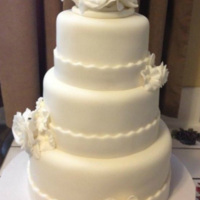 Three-Tiered White Wedding Cake With Roses Simple three-tier white wedding cake. It is covered in fondant and the roses in the topper and on the tiers are made from gum paste. It was...