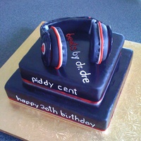 Dj Birthday Cake 2 tier chocolate cake iced in chocolate fondant coloured black. Gumpaste headphones on top.