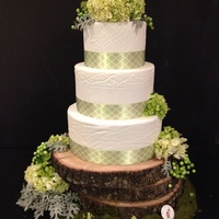 The Dusty Rustic styled wedding cake featuring fresh flowers, sugar grapes, and ribbon on a 3 tiered fondant cake with inscribed details