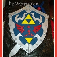 Zelda Shield And The Master Sword This cake was carved from a 16x16x2 cake. The sides were covered with black fondant. The top decorations were cut from modeling chocolate!...