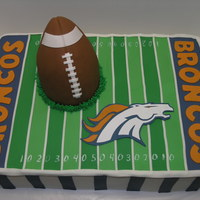 Denver Broncos 12 X 18 frosted with buttercream and fondant accents. Handcut Bronco from fondant. Football is made of RKT. Thanks for looking!