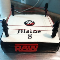 Wwe WWE wrestling cake, used black fondant on sides and dowel rods covered in fondant for poles. took Red string and pulled them tight.