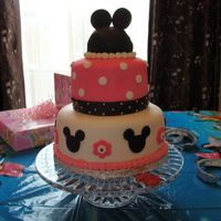 Minnie Mouse Birthday Cake Tiered birthday cake with minnie mouse ears made with oreo cookies. All fondant accents.