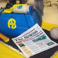 Indoor Track Banquet 2011 Track small duffle bag with a water bottle (rice treats covered in modeling chocolate) sticking out of top, newspaper (printed frosting...