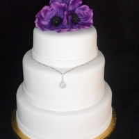 Jewels Cake Purple Flowers with grandmothers antique necklace attached to tier.