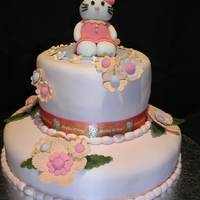 Hello Kitty With Flowers - Birthday Cakae   Kitty and her flowers are made from gumpaste. The cake is covered in fondant and a decorative ribbon was added between the tiers.