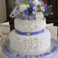 Shades Of Blue Birthday Cake An assortment of blue flowers were made from gumpaste. The cake was covered in buttercream and enhanced by a blue ribbon and jeweled button...