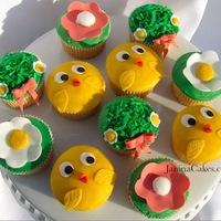 Easter Cupcakes Chicks are made with colored modeling chocolate. Big flower cupcakes are covered with green icing and topped with a fondant flower. Green...