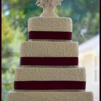 4 Tiered Plum Square Scrolled Wedding Cake 6, 8, 10, 12 squares alternating chocolate & white cake buttercream frosted/filled/decorated. Plum ribbon backed with wax paper around...