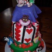 Alice In Wonderland Cake Its a three tier whimsical cake with foam spacers in between the tiers. Everything on the cake was made with either fondant or a...