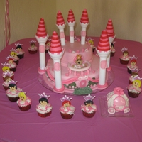 Pink Castle 2 tier cake with cupcakes and minicake carriage. princess and heads on cupcakes are made of fondant