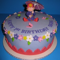 Sara's First Birthday Cake The birthday girl loves rain, so I make this cake with a little fondant figure of Sara in her rain boots, raincoat and pink umbrella.