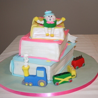 Stacked Book Cake  This is a stacked book cake done with Humpty Dumpty sitting on top, The little engine that could going around, The dish and the spoon and...