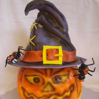 Jack-O-Lantern Cake With Hat Here is a Jack-O-Lantern cake with a witch's hat. The spiders and hat buckle are gumpaste. Laces on the hat are licorice.