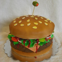 Hanburger Cake Cake that looks like a hamburger I made for a burger cook-off. Buns covered in fondant. Burger patty frosted with chocolate frosting....
