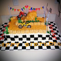 Butter Pecan Cake With Buttercream Frosting Track Is Covered In Crushed Graham Crackers Motocross Jump Is Made From Rice Krispie Treats Co... Butter Pecan cake with buttercream frosting. Track is covered in crushed graham crackers. Motocross jump is made from Rice Krispie Treats...