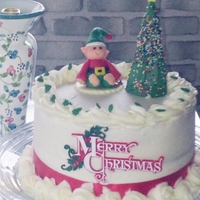 Almond Vanilla Cake Covered In Almond Buttercream And Topped With Fondant Elf And Royal Icing Christmas Tree Almond vanilla cake, covered in almond buttercream and topped with fondant Elf and royal icing Christmas tree.