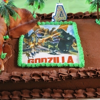 Godzilla 1/4 sheet chocolate buttercream ricecrispy montains covered in fondant that have been airbrushed an a ricepaper image