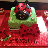 Abby's 1St Birthday Vanilla cake with raspberries & cannoli filling. Vanilla BC. Fondant accents.Ladybug body is also cake, head is RKT.Cupcakes on the...