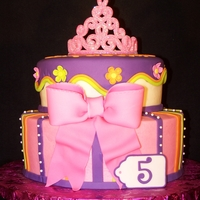 Pink Princess two tier cake with princess crown, stripes and flowers.