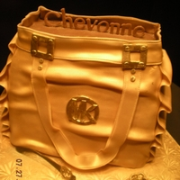 Michael Kors Bag Cake  Cake is French Vanilla with French Vanilla Buttercream. Covered in fondant and sprayed gold. The buckles and other gold accents were...
