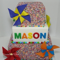 Sprinkle Cake For My Little Boy! My son turned 4; and he loves sprinkles and pinwheels. Best way to cover a cake in sprinkles is with piping gel.