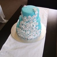 Blossom Wedding Cake   3 Tier choc cake filled with choc buttercream, covered in fondant and flower paste blossoms. TFL