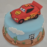 Lightning Mcqueen And Route 66 This cake was for a super Lightning McQueen fan. The car is made of RKT, then covered with modelling chocolate to shape and then fondant....