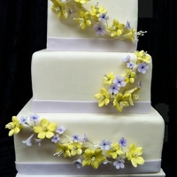 Lavender And Yellow Blossoms Cake This is a 3 tier anniversary cake with lavender and yellow blossoms cascading along the cake.
