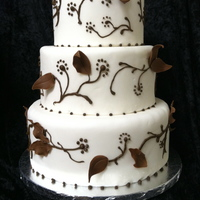 Chocolate Leaves This is a three tier wedding cake decorated with chocolate leaves and piping details.