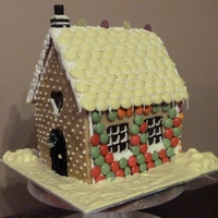 Cookie House   Ginger flavoured cookie covered in sweeties with sugar stain glass windows with battery light