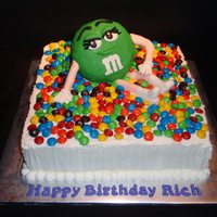 Green M&m Lady M&M made of RKT covered in fondat. Legs and arms are lollipop sticks covered with fondant.