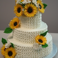 Molloy/davis Wedding Cake Three tier (white, chocolate, white) cake with gumpaste sunflowers, white roses, stefanotis and babies breath. Petal affect icing.