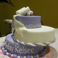 Purple And White Yellow CME with vanilla buttercream and MMF. Fondant with added Tylose for the bow.