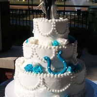 Colts Wedding Cake   Full buttercream cake including buttercream roses and a handmade Colts horseshoe. Topper by couple