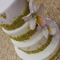 Fondant Covered Cake With Gold Dragees Sugar Made Orchid Fondant covered cake with gold dragees. Sugar made orchid