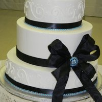 Black Ribbon With Blue Brooch White cake with scrolls, black ribbon and blue brooch