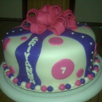 "Pink And Purple Ribbon Cake 10"" round covered in fondant with fondant accents. Loopy bow is fondant as well."