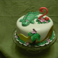 Girl Dinosaur Cake vanilla cake with raspberry filling and cream cheese icing. All fondant decorations.
