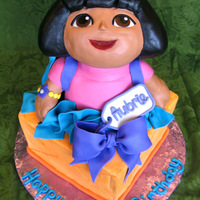 Dora  Dora's head and arms are RKT covered in fondant mixed with tylose. Dora's body and the present are chocolate fudge cake with...