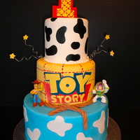 "Toy Story Cake This is a three tiered (9"", 6"", 4"") cake coated in Sugar shack buttercream and covered in Fondx Fondant. The decorations are..."
