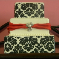 "Black And White Damask 3 tier square 6"", 8"", 10"" damask pattern stenciled with black royal on top and bottom tier. Red fondant drapes and pearl..."