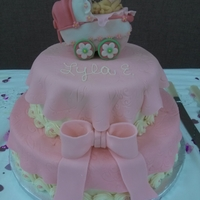Baby Girl Shower Cake Butter cake iced in Buttercream. Fondant is used only for the pink blankets over the tiers, the rice krispy carriage and the baby and for...