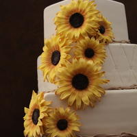 Sunflower Wedding Cake Bride wanted a rustic cake with raffia and sunflowers. Everything is fondant except for the toppers which were wood signs. Sunflowers were...