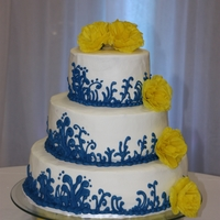Blue And Yellow Wedding Cake   White buttercream frosting with blue scrolls and yellow silk flowers