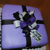 Present Chocolate cake with Chocolate Bavarian Cream. Covered in buttercream with fondant bow and accents. Colors were lavender, black and silver
