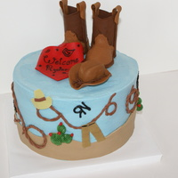 Western Shower Cake   8 inch round cake with blue buttercream icing. Fondant western theme decorations and gumpaste boots, cowboy hat, and bandana.